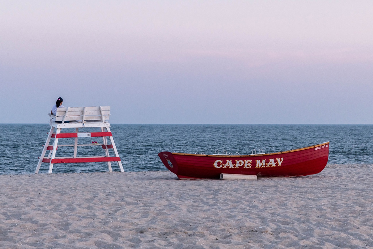 A lifeguard stand and Cape May red lifeguard boat at the beach with pink skies