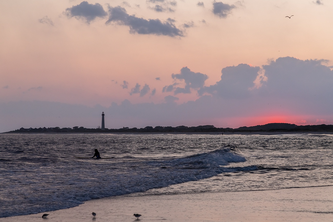 A surfer out in the ocean watching the sun set below the horizon with the Cape May lighthouse in the distance and birds at the shoreline
