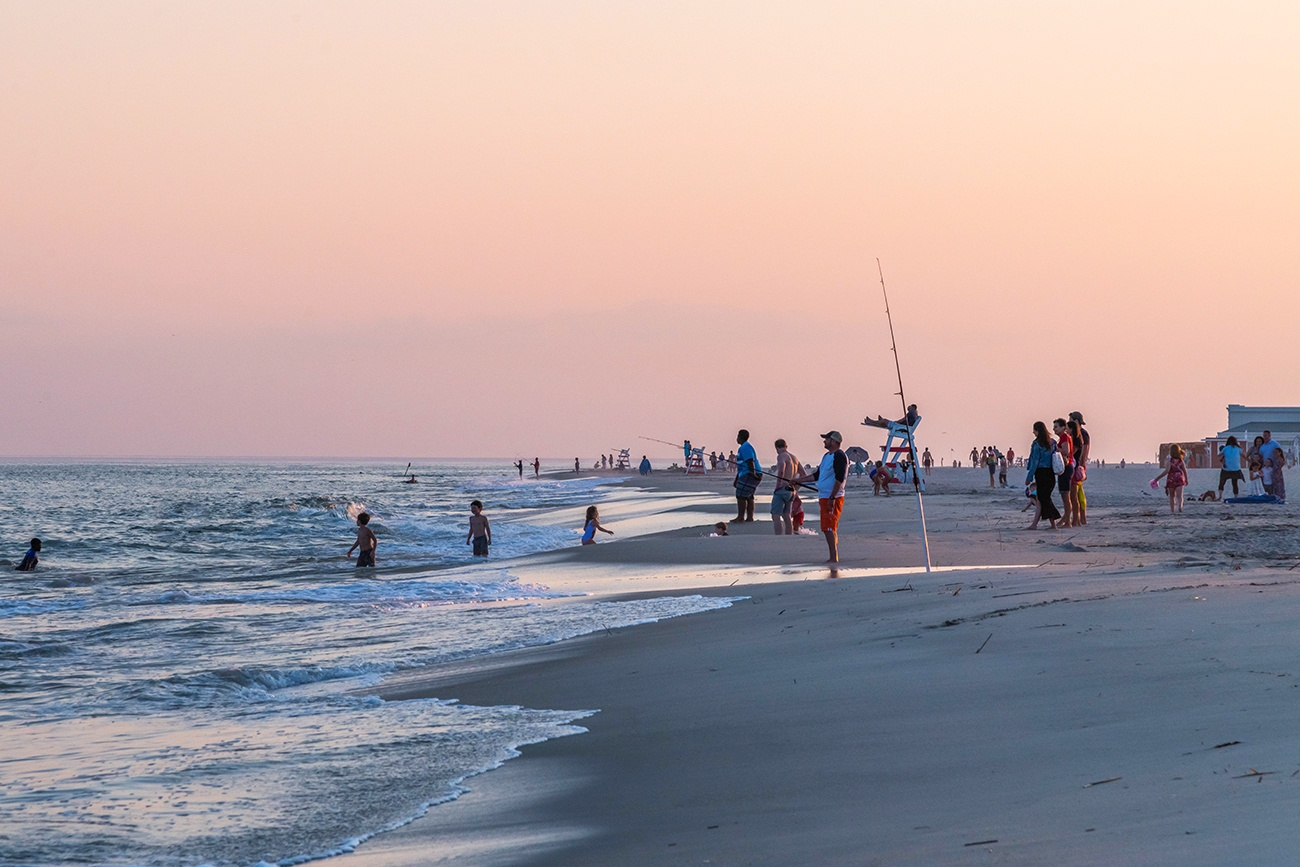 People fishing, swimming, and gathered by the ocean at sunset