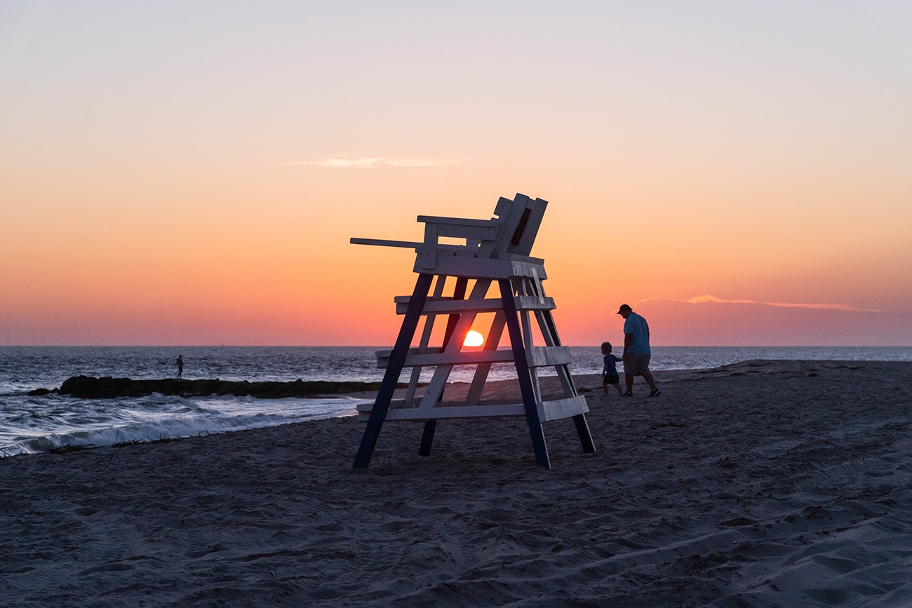 The sun setting behind a lifeguard stand as a father and child walk on the beach