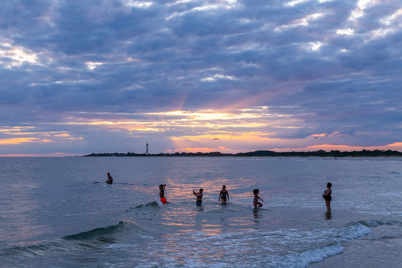 Kids playing in the ocean and a person on a surfboard as the sun sets behind clouds with the Cape May lighthouse in the distance