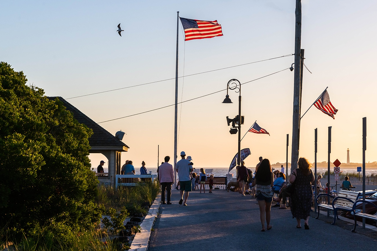 People walking on the promenade at sunset with American flags flying