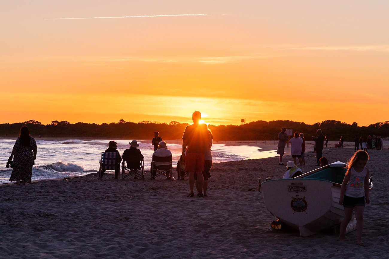 Groups of people watching the sun set at the beach