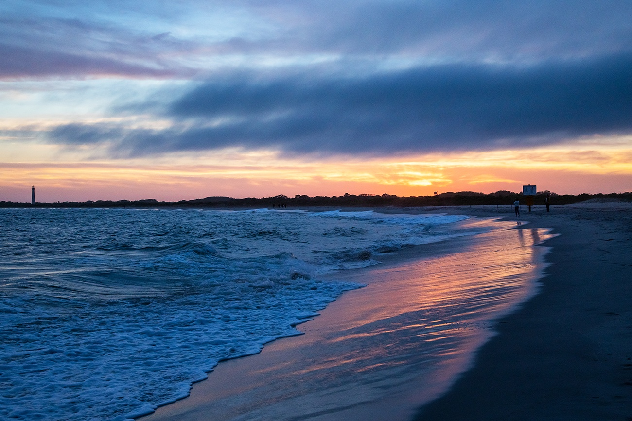 Clouds at the horizon at sunset on the beach with the Cape May lighthouse in the distance