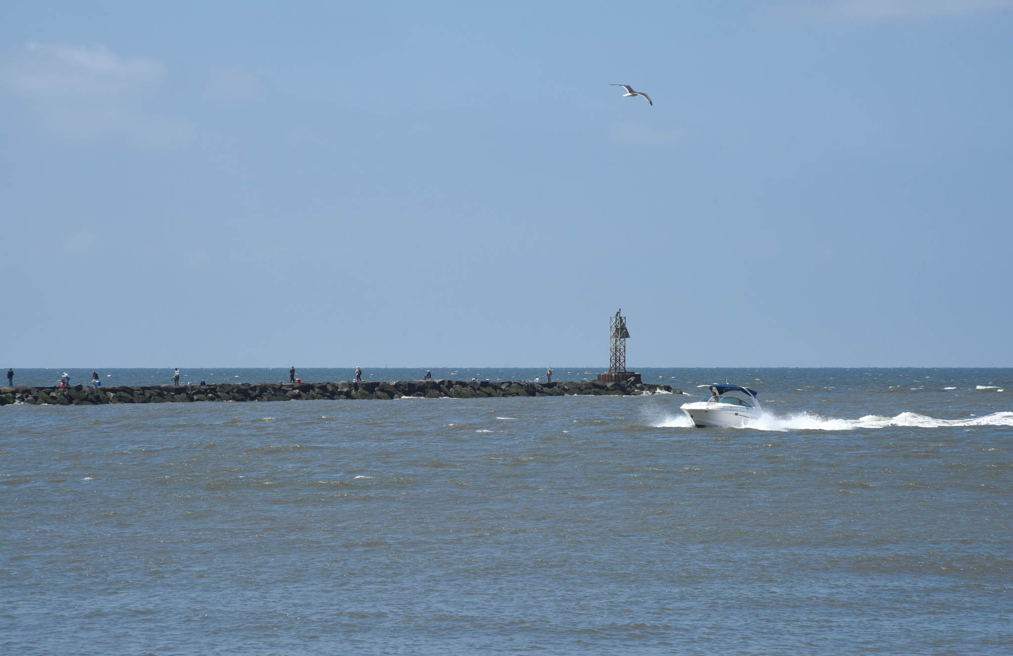 A boat heading back to the harbor, people fishing on the jetty