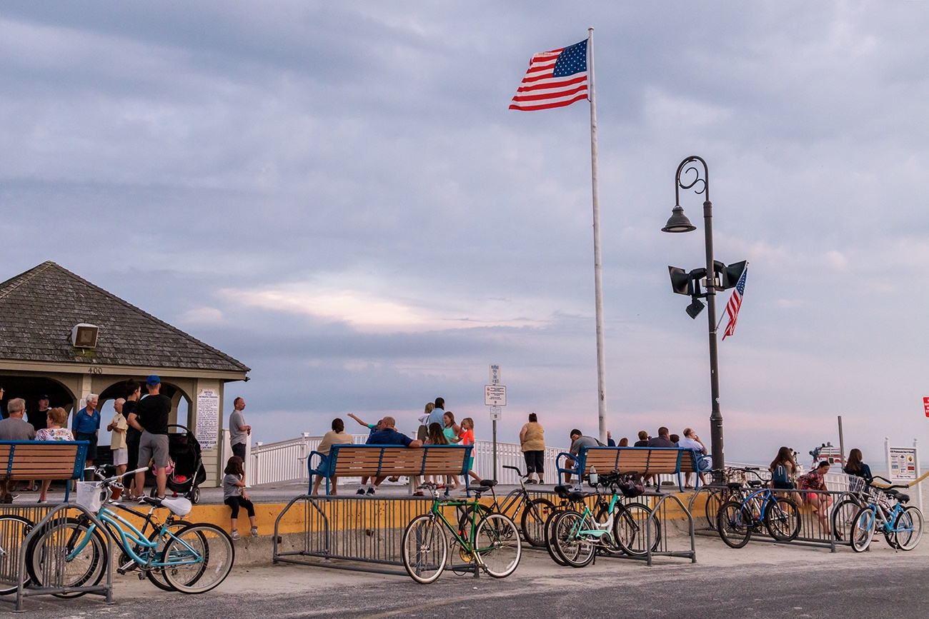 People sitting and bikes lined up at the end of the Promenade with an American Flag waving