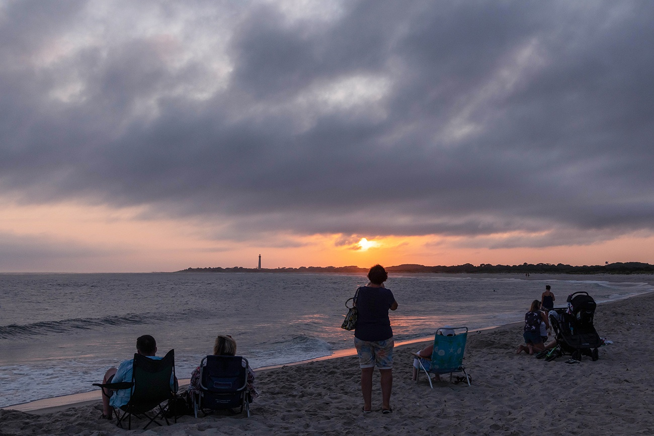 Sun setting with clouds in the sky with people sitting on the beach