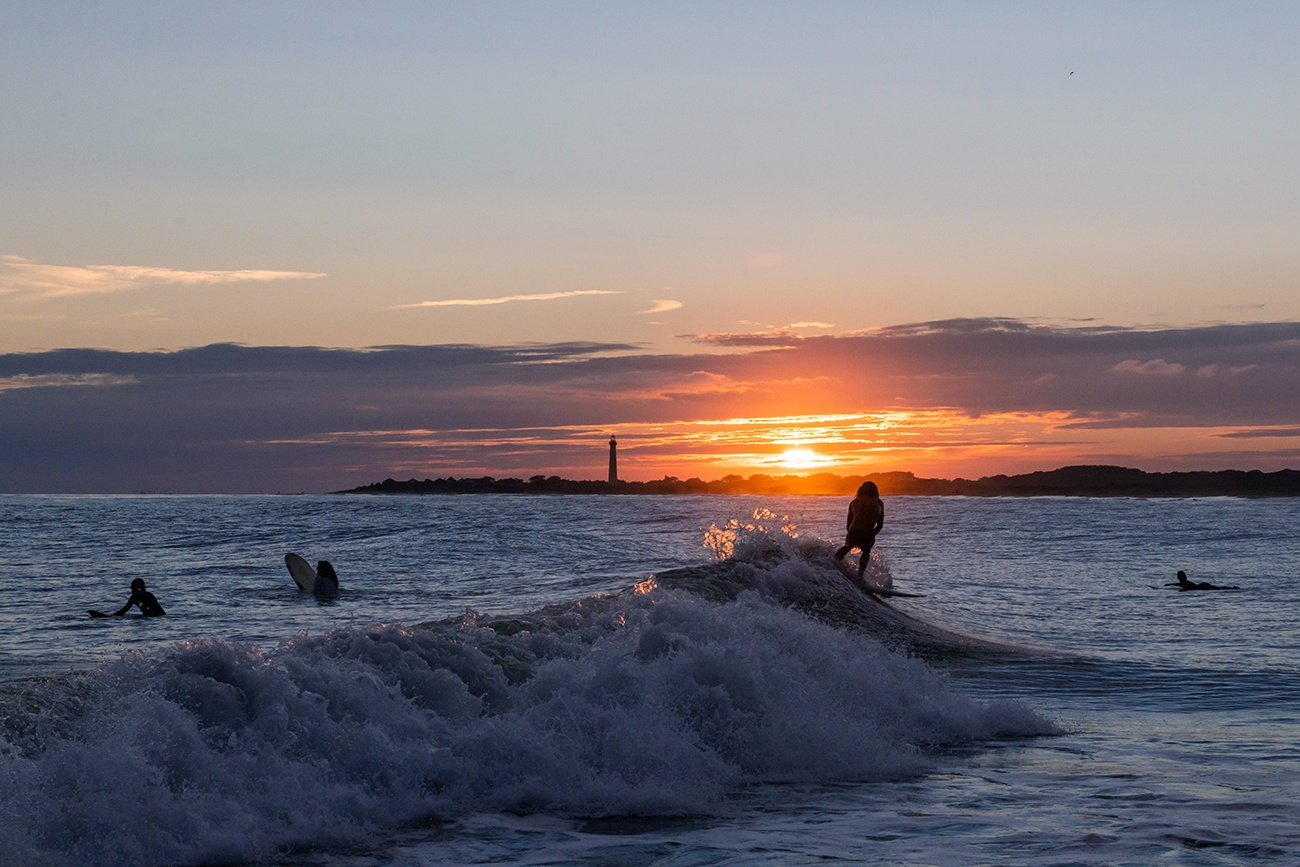A person surfing a wave as the sun sets by the Cape May lighthouse.