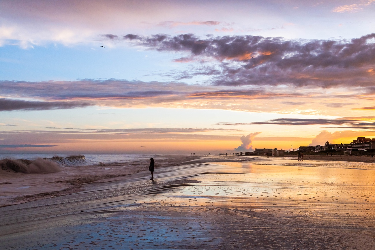 A person standing at the water during high tide as waves crash along the shore at sunset