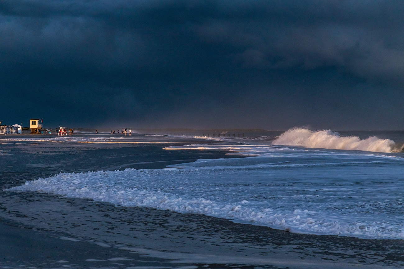 Big waves crashing during an extreme high tide with dark clouds in the sky