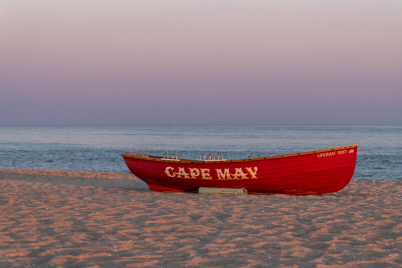 A red Cape May lifeguard boat on the beach at sunset