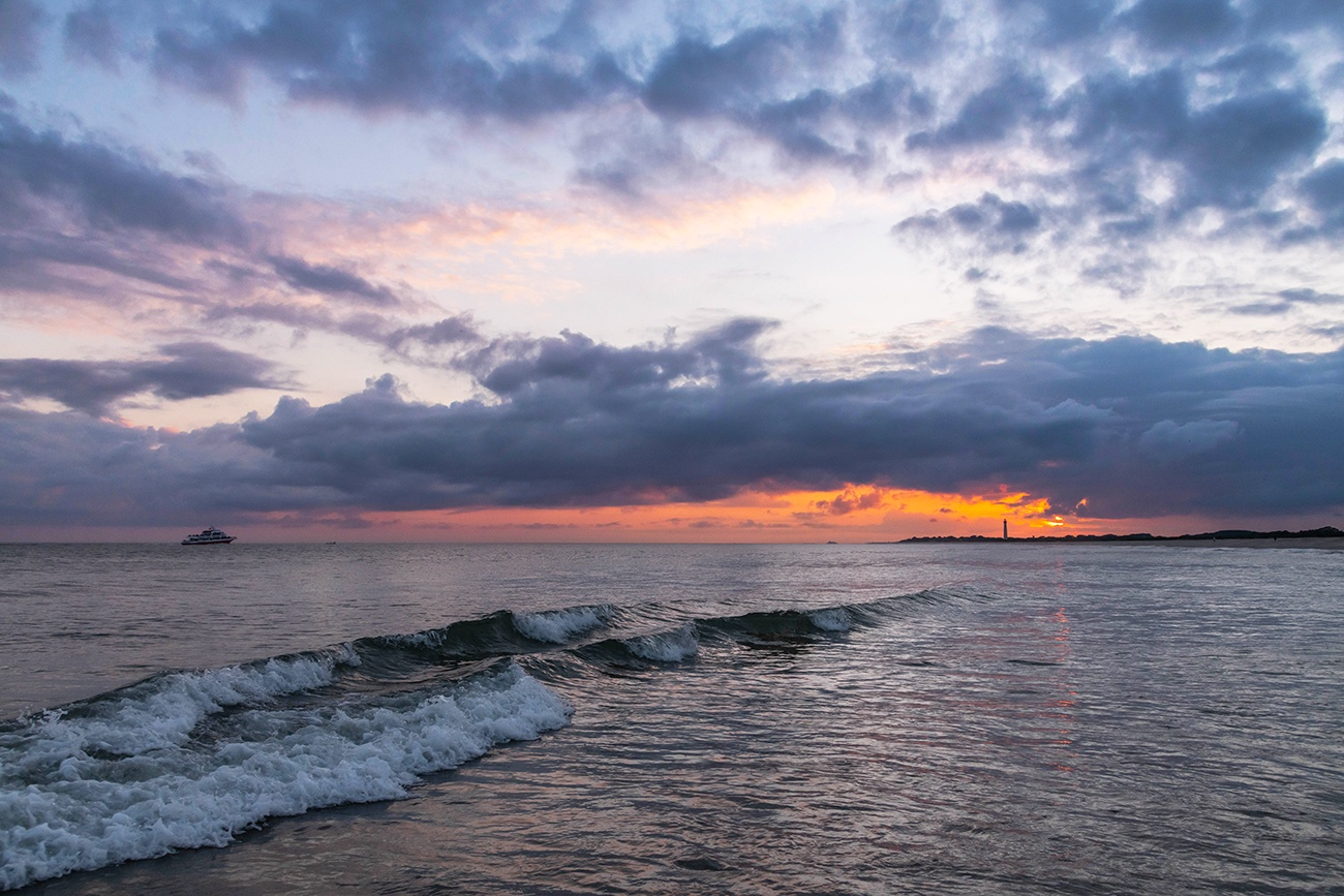 Purple clouds moving in the sky at sunset over the ocean with an orange streak of light at the horizon