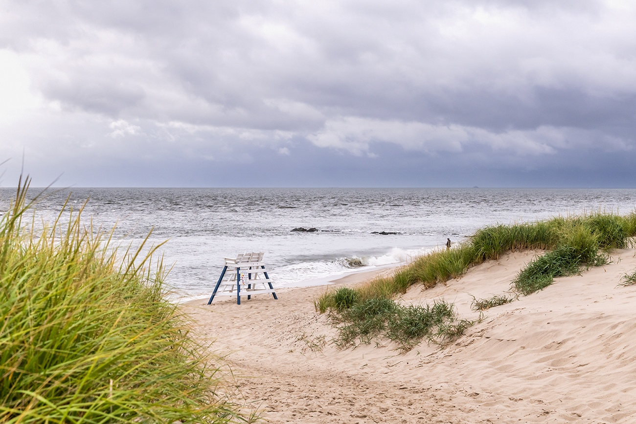 A lifeguard stand at the end of a sand path to the beach with dark clouds in the sky