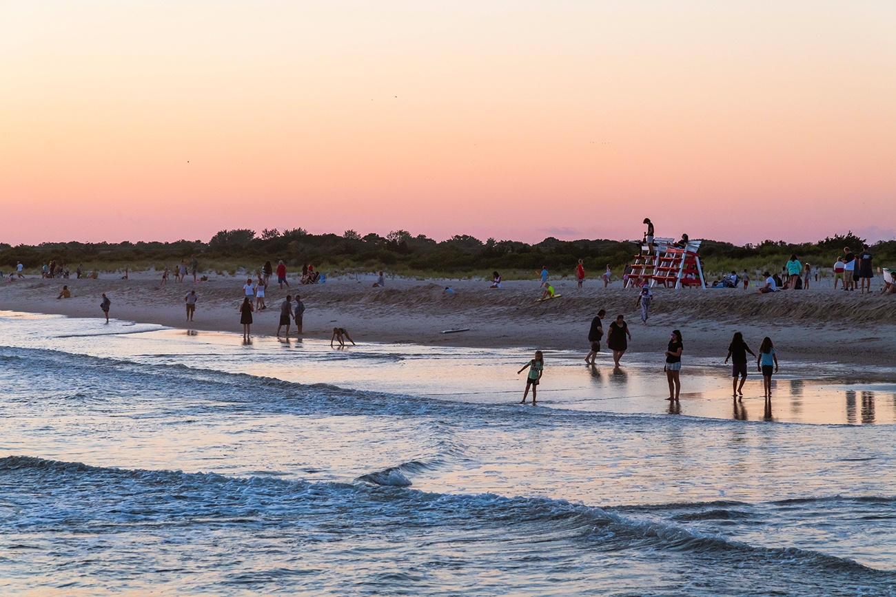 People walking by the ocean and playing in the sand at sunset