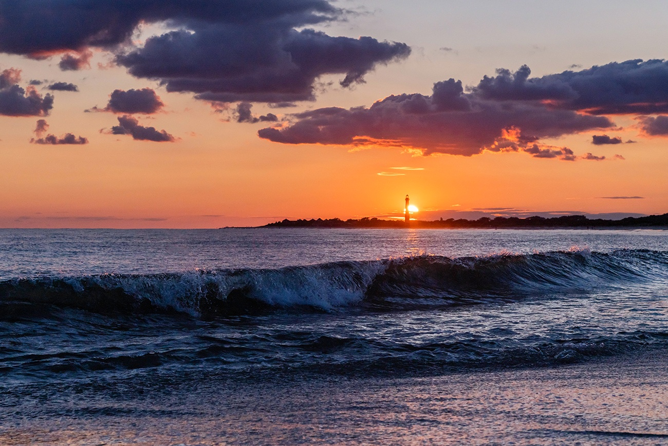 The sun setting directly behind the Cape May Lighthouse with a wave crashing