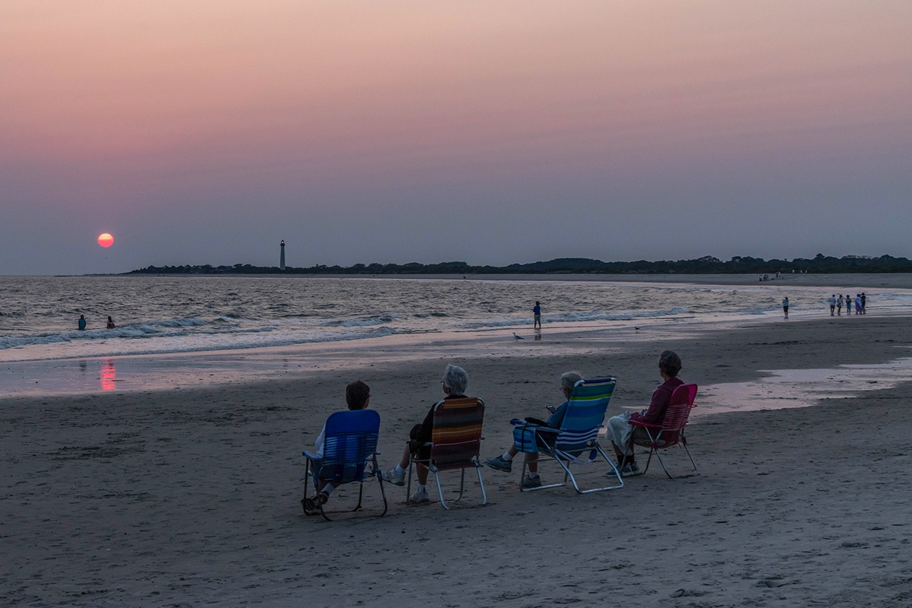 Four people sitting on the beach watching the sun set with the Cape May Lighthouse in the distance