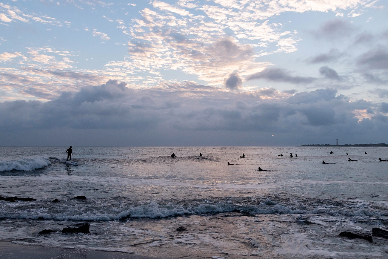 Surfers out in the ocean with clouds in the sky at sunset