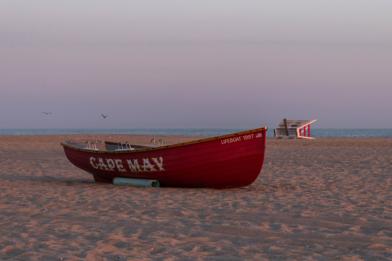 A red Cape May lifeguard boat on the beach with a lifeguard stand down on it's side in the distance at sunset