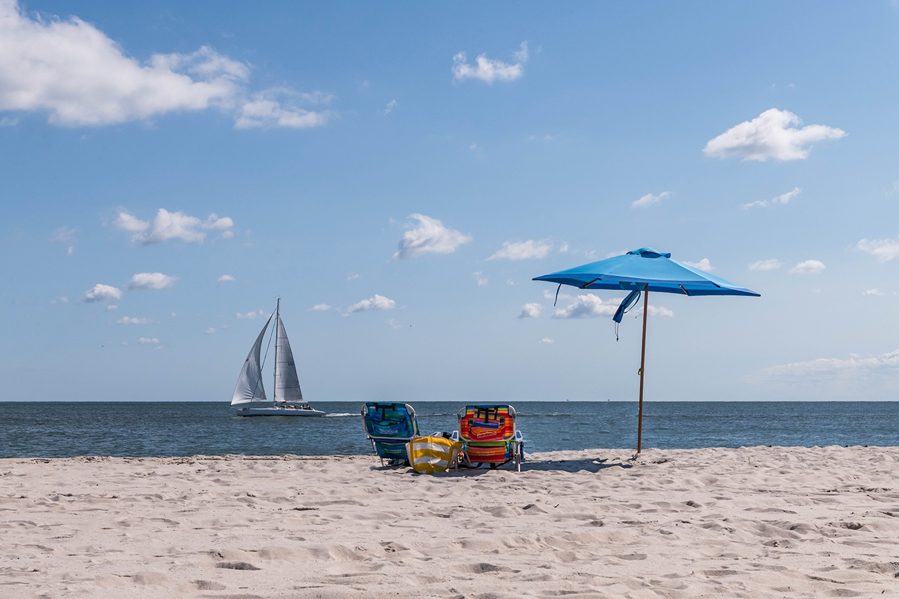 A blue umbrella on the beach with beach chairs and a sail boat on the ocean on a sunny blue sky day