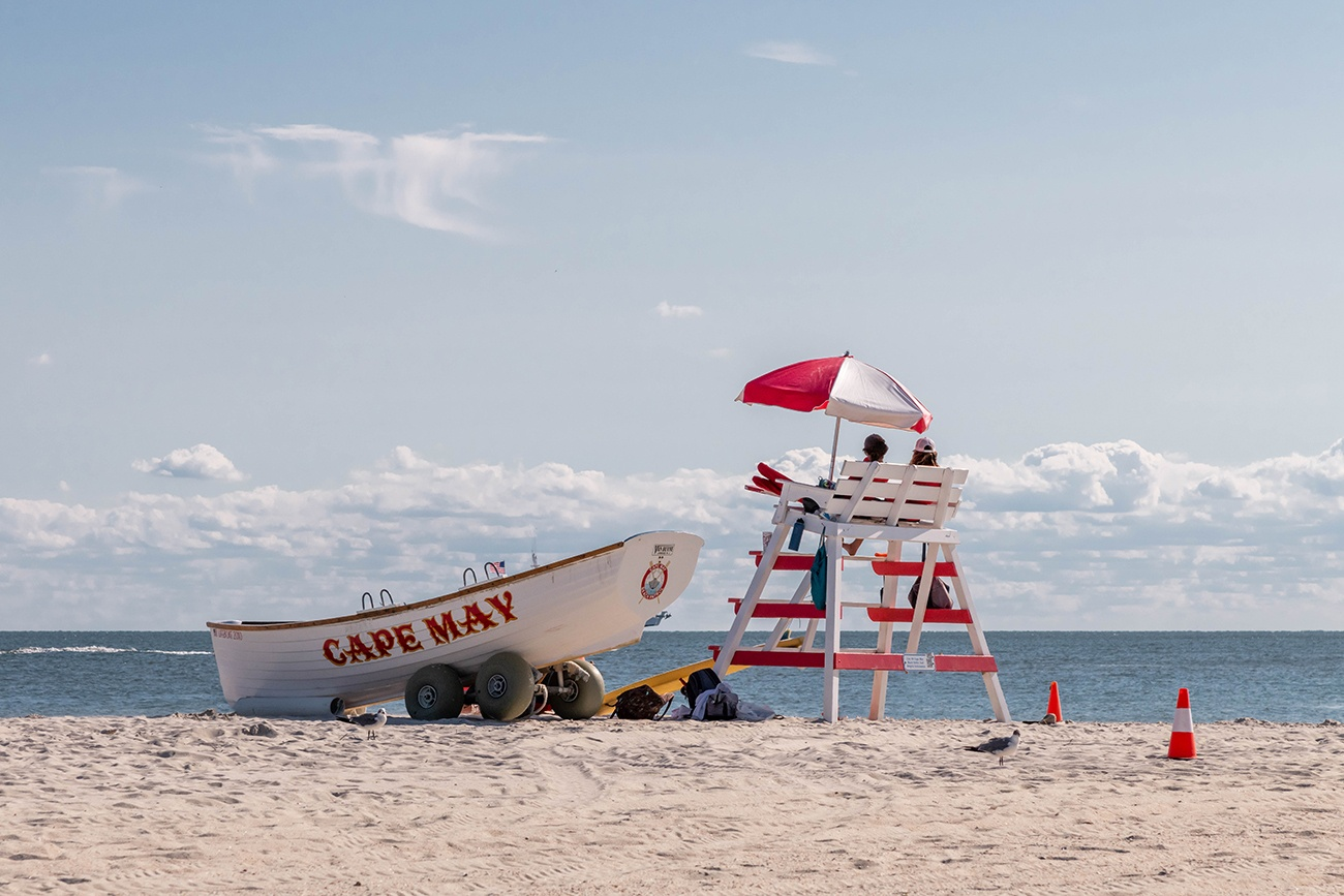 Two lifeguards sitting on a lifeguard stand with an umbrella and a Cape May lifeguard boat on the beach on a clear blue sunny day