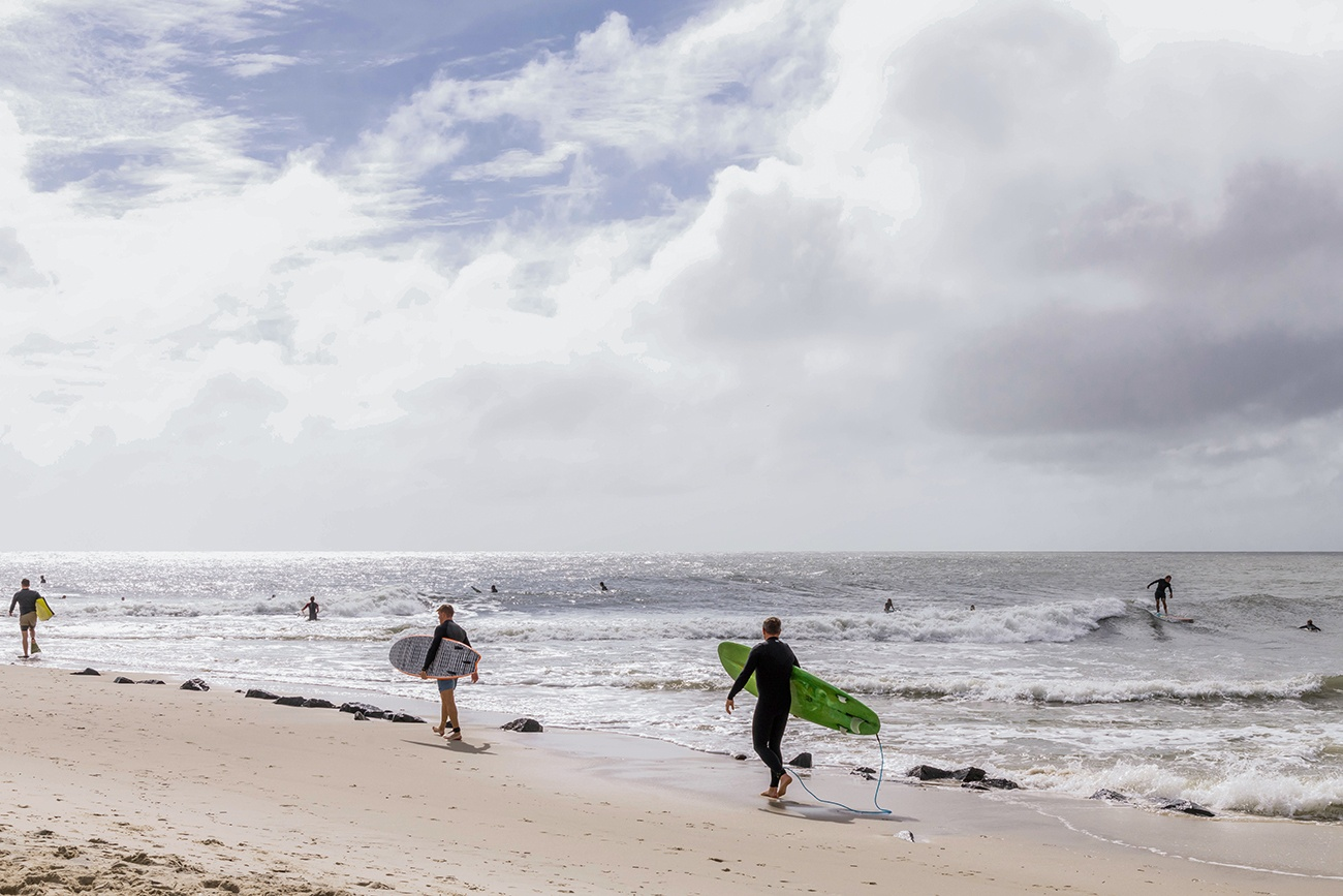 Three surfers walking out to the ocean while other surfers are out in the ocean with clouds and sun in the sky