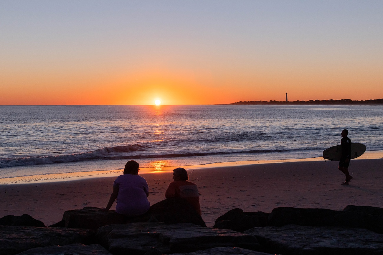 Two people sitting on the jetty watching the sun set as a surfer walks to the ocean with the Cape May Lighthouse in the distance