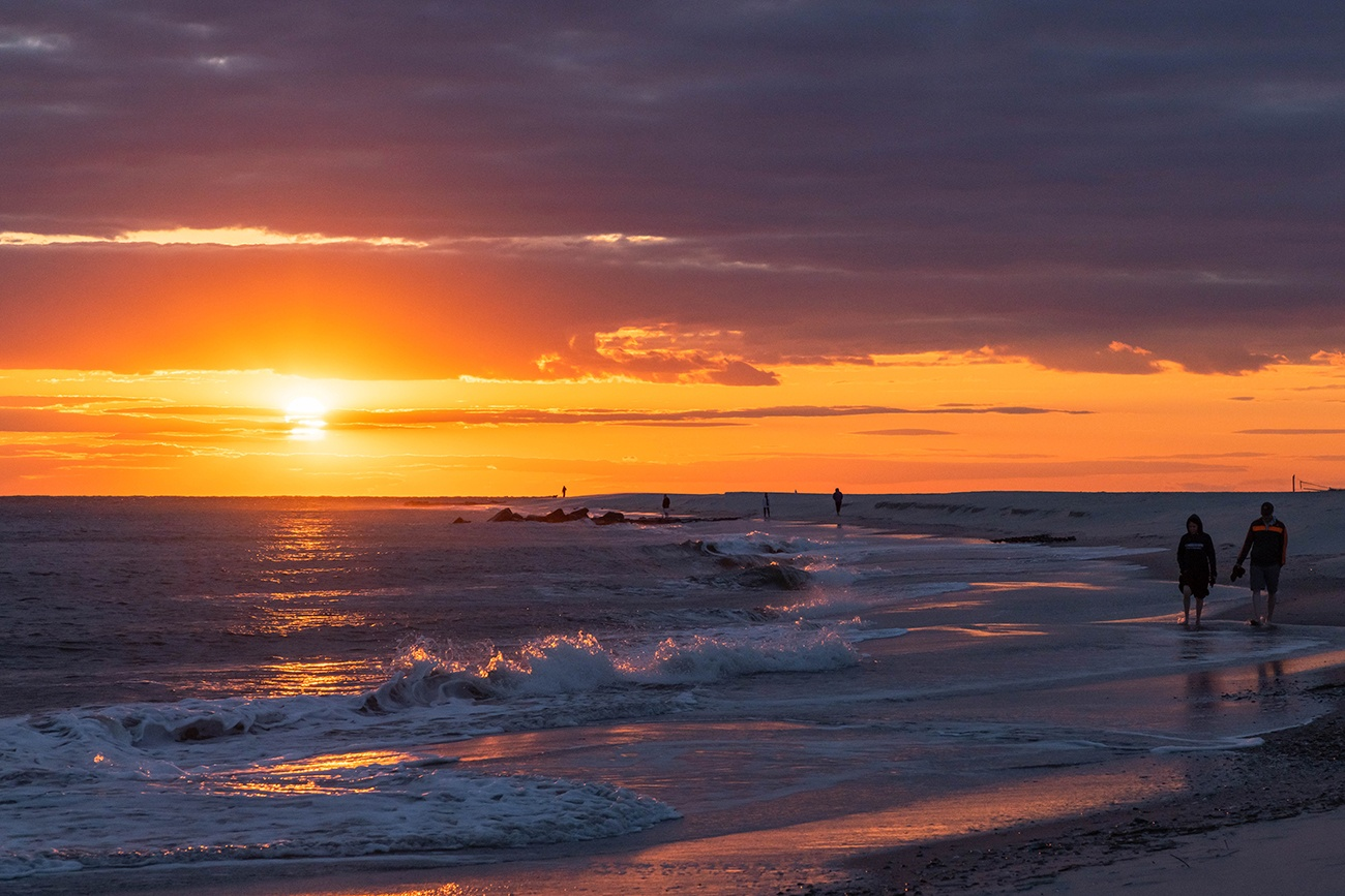 People walking by the ocean as waves crash along the shore and the sun sets with clouds in the sky