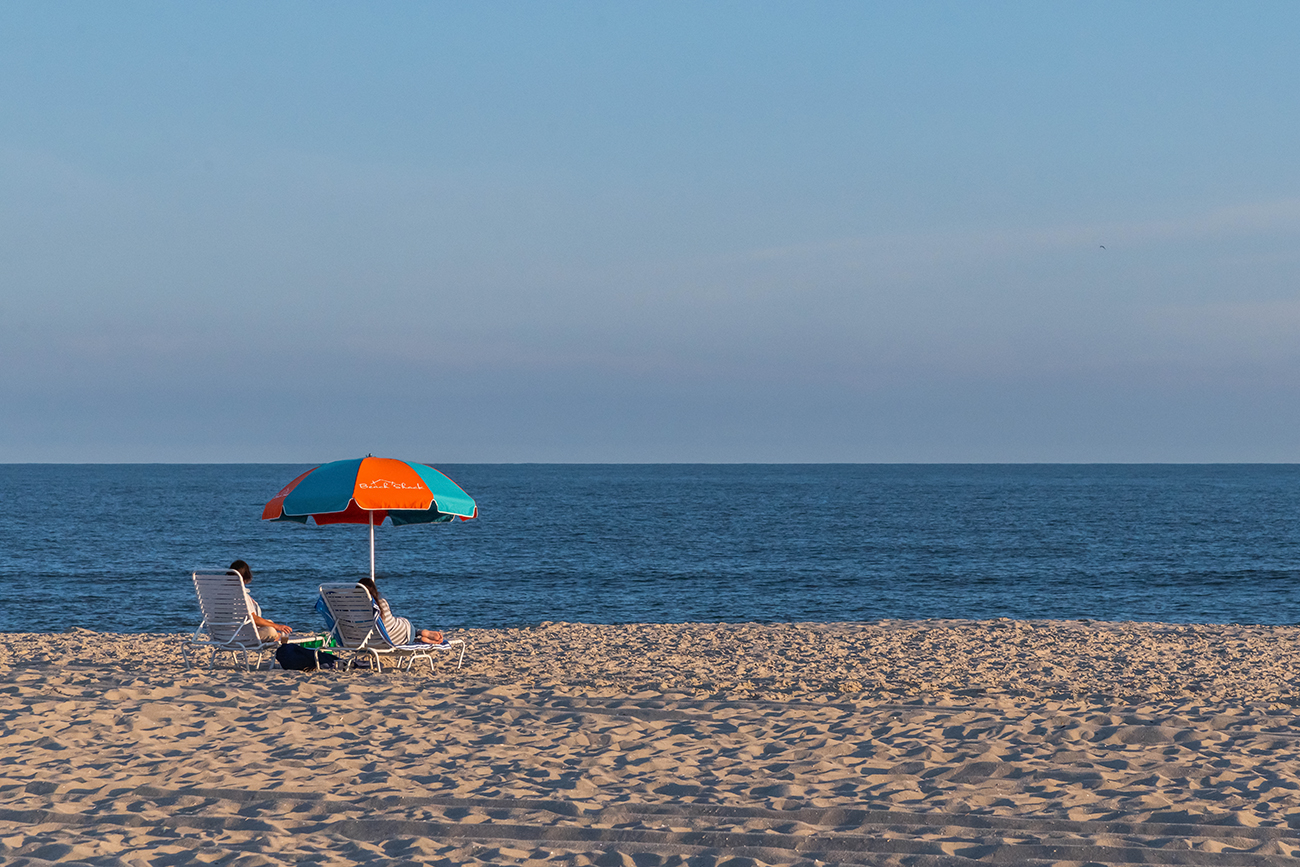 Two people sitting on the beach at the end of the day under an orange and blue umbrella